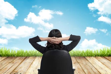 Hombre de negocios que se sienta en la silla mirando el cielo azul Foto de archivo