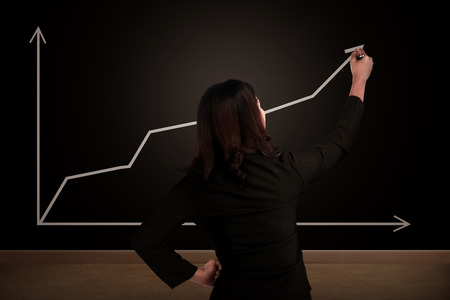 back arrow: Business woman drawing increasing chart on the chalk board. Business success concept Stock Photo