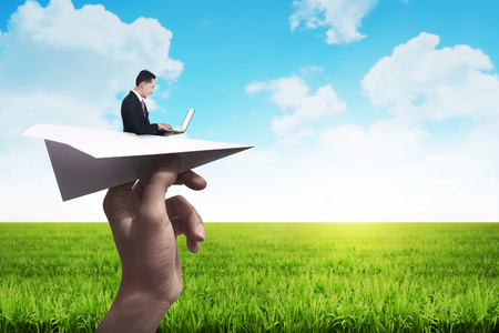ideas: Business man typing with laptop on the paper plane ready to fly