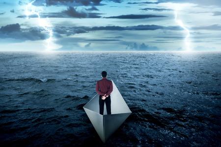 cielo y mar: Hombre de negocios de pie solo en barco de papel, mirando el horizonte