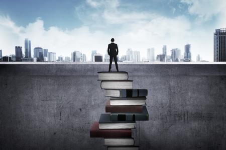 образование: Вид сзади деловой человек, глядя на город, стоящий на верху книги. Образование для успеха концепции