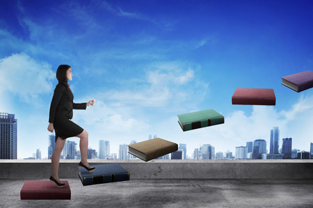 up stair: Business person step up flying book that look like stair. Career and education concept Stock Photo