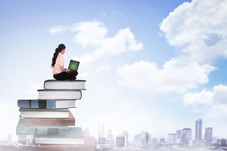 образование: Деловой человек, работать с ноутбуком на верхней части книг. Карьера и образование концепция