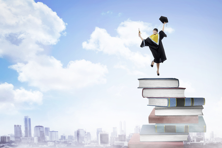 Asian woman student, graduation from college, jumping on the stack of book Stock Photo
