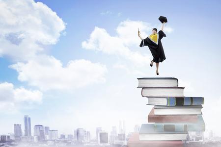 colegios: Estudiante mujer asiática, graduación de la universidad, saltando sobre la pila de libros Foto de archivo