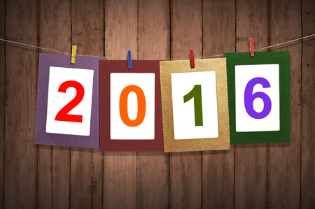 calendrier: New year 2016 in photo frame hanging on clothesline with wood background