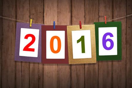 calendario: Nuevo a�o 2016 en el marco de fotos colgando de tendedero con el fondo de madera