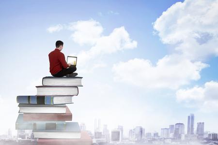 Bedrijfspersoon die met laptop op de bovenkant van boeken werkt. Carrière en onderwijs concept