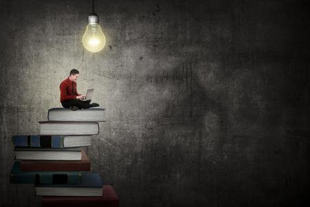 Aziatische zakenman werken met laptop zitten op de top van het boek. Idee en kennis concept Stockfoto
