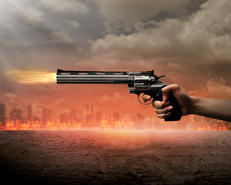 Man hand holding gun and aiming to the burn city