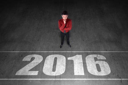 person looking: Business person looking 2016 number on the floor. New year resolution concept