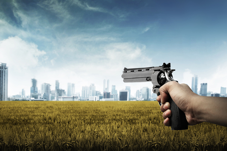 man holding gun: Man hand holding gun, aim to the city