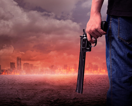 aiming: Man hand holding gun with burn city background Stock Photo