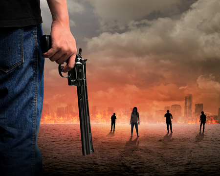 Man hand holding gun with zombie and burn city background