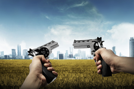 aiming: Man hand holding two gun, aiming to the city