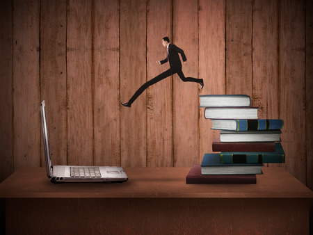 modernize: Concept of technology migration with business person jumping from book to laptop