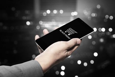 Mano che tiene il cellulare con testo nero venerdì e carrello della spesa Archivio Fotografico - 46939905