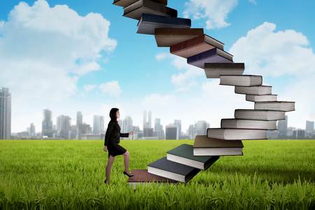 step up: Business person step up flying book that look like stair. Career and education concept Stock Photo