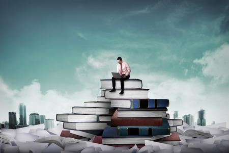 Persona de negocios asiática que trabaja con ordenador portátil se sientan en la parte superior del libro. Idea y el conocimiento concepto Foto de archivo - 46939939