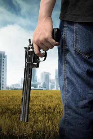 Man hand holding gun on the green field