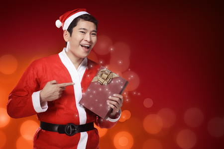 male costume: Handsome asian man wearing costume as santa claus, holding gift box