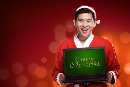 male costume: Handsome asian man wearing costume as santa claus and holding laptop with merry christmas writing