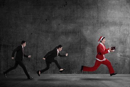 Business people chasing santa claus. Christmas bonus concept