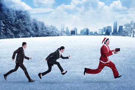 hombres corriendo: La gente de negocios que persiguen santa claus. Concepto de aguinaldo