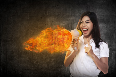 beautiful angry: Asian business woman with a megaphone shouting megaphone on fire Stock Photo