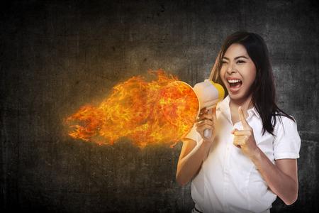 mujer enojada: Mujer de negocios asiática con un megáfono gritando megáfono en llamas