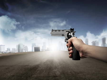 aiming: Man hand holding gun, aiming to the city Stock Photo