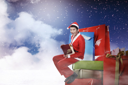male costume: Young asian man wearing santa claus costume sit on the big present box
