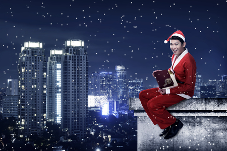 christmas costume: Asian man wearing santa claus costume sit on the rooftop. Christmas present