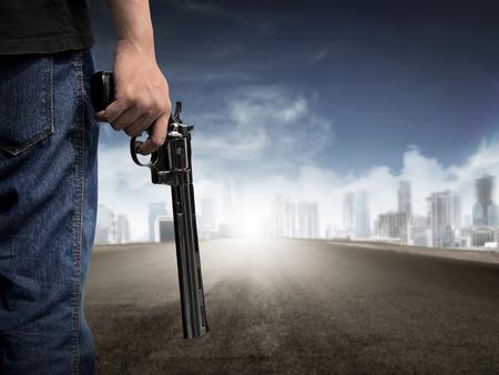 Man hand holding gun on empty highway