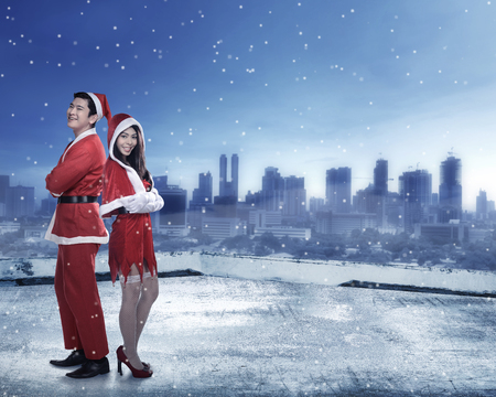 christmas costume: Happy couple in santa claus costume standing on the building rooftop. Christmas couple concept