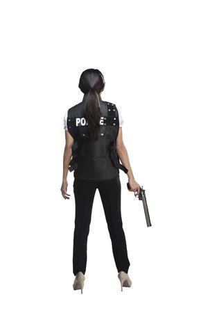 mujer con pistola: Vista posterior de la mujer que sostiene el arma aislado en el fondo blanco Foto de archivo