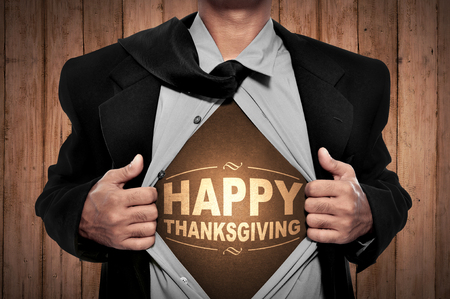 super man: Business man tears open his shirt in a super hero fashion with happy thanksgiving writing