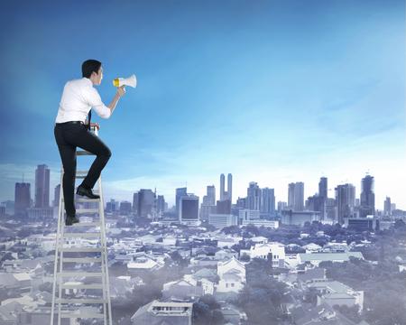megafono: Asia hombre de negocios de pie en la escalera, la celebraci�n de meg�fono. Concepto Leadershop