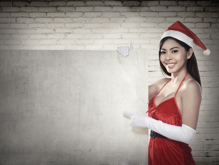 christmas costume: Asian woman in santa claus costume holding blank banner. Christmas concept