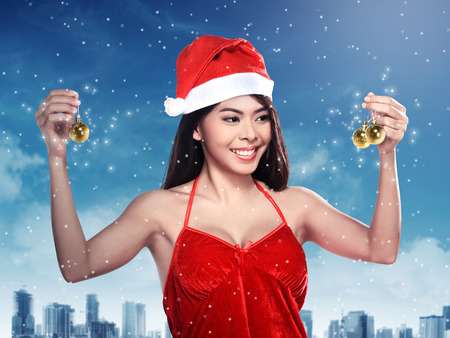 costume ball: Pretty woman in santa claus costume holding christmas ball. Merry christmas concept
