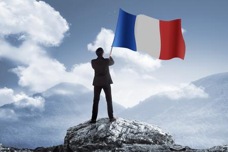 Man die vlag van Frankrijk staande op de top van de berg Stockfoto