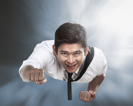 flying man: Handsome young asian business man flying through the sky Stock Photo