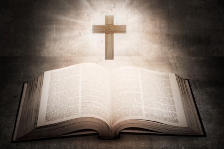 cruz religiosa: Santa Biblia abierta con una cruz de madera en el medio. concepto cristiano Foto de archivo
