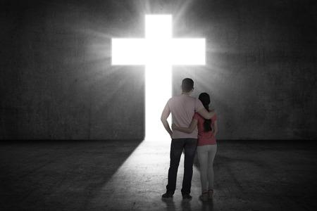 religion catolica: Pareja joven busca la cruz que brilla en la pared. concepto religioso Foto de archivo