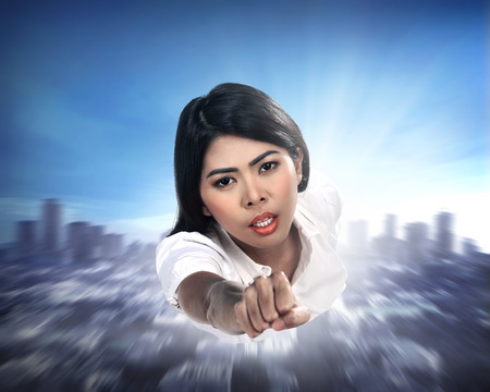 supergirl: Beautiful young asian business woman flying through the sky Stock Photo