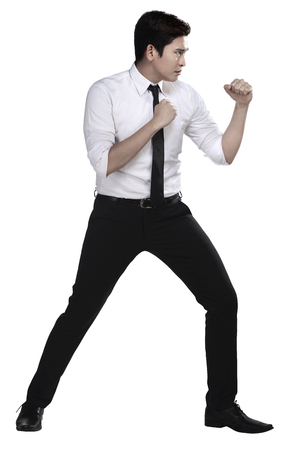 fighting: Man in white shirt doing fighting stance on white background Stock Photo