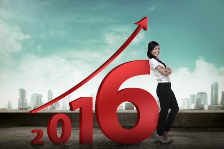 mujer trabajadora: Persona de negocios asi�tica inclinarse junto a 2.016 n�mero. Concepto de resoluci�n A�o nuevo Foto de archivo