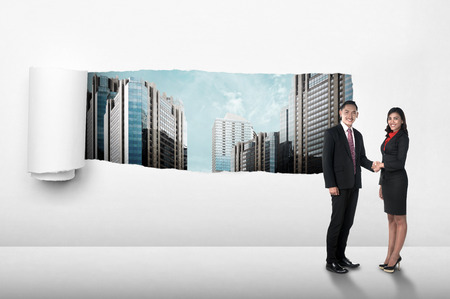 lagrimas: Asian business people shaking hand over paper tear background
