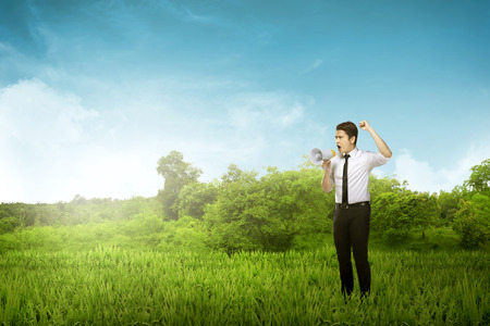yell: Asian  business man yell using megaphone over woods background Stock Photo