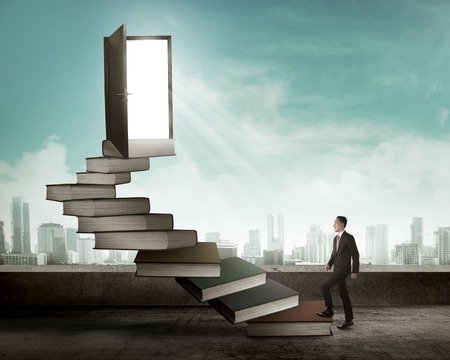 up stair: Asian business man stepping up stair made from book. Business knowledge concept